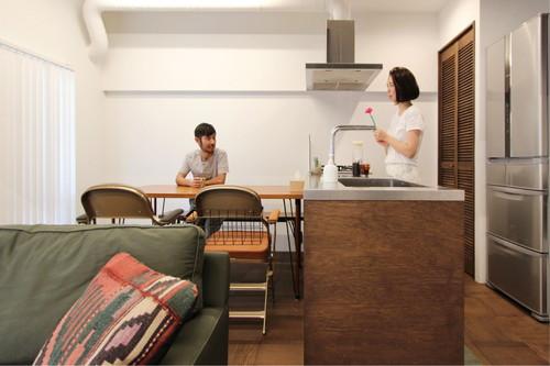 腰壁に木を貼った造作キッチンとダイニングでおしゃべりを楽しむお二人。