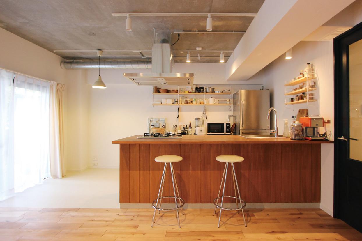 腰壁と天板に木を使った造作キッチン。スツールを合わせるとそこはまるでカフェのような空間に。