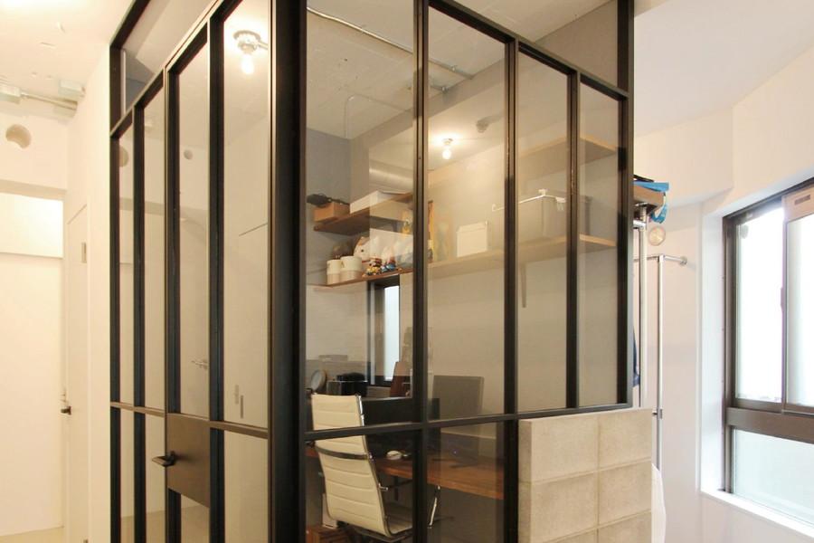 黒の格子とコンクリートブロックがラフな印象を与えるガラス張りのワークスペース。