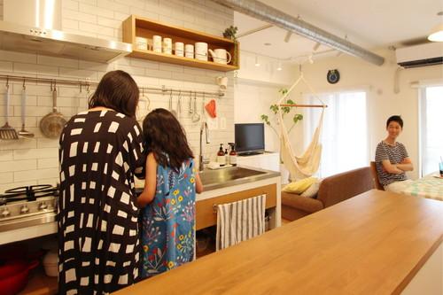 木のあたたかい雰囲気が漂う造作キッチンでお料理を楽しむ奥様とお子様。