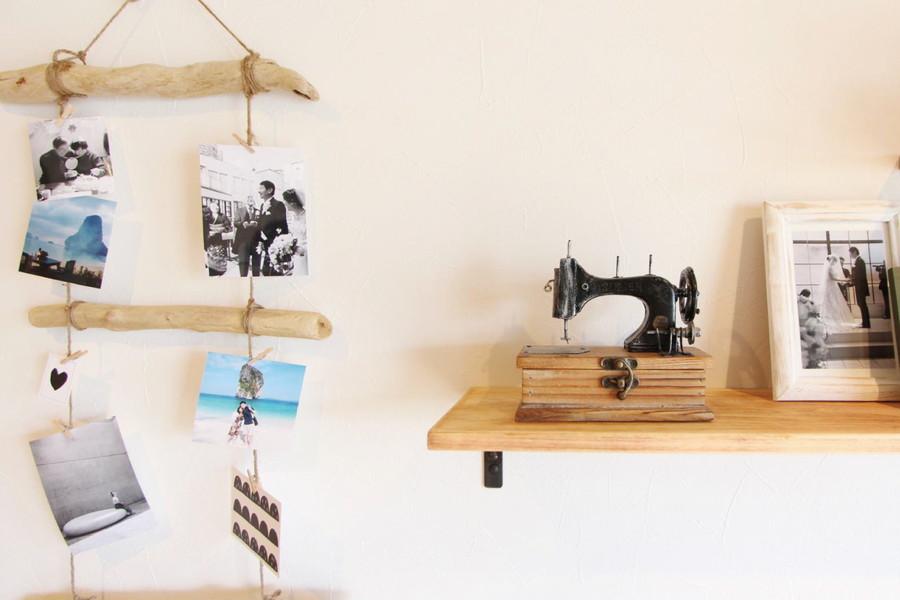 DIYで取付けた壁面棚と、流木と麻ひもを組み合わせた写真掛け。