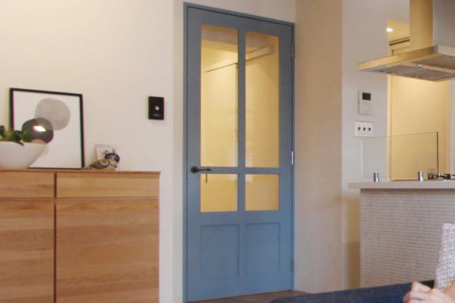 ブルーグレーの扉にはガラスをはめ、取手はアンティークのドアノブをプラス。